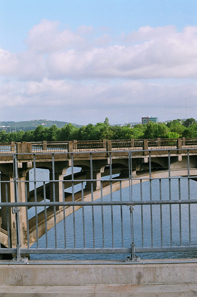 The scenery -- the old Lamar Bridge and beyond. <br /> <br /> For more than 50 years, the historic Lamar Boulevard Bridge carried cars, runners, walkers, and bicyclists over the section of the Colorado River known as Lady Bird Johnson Lake (formerly Town Lake). But over the years, as the volume of cars increased on the narrow roadway, the bridge became treacherous for pedestrians and bicyclists. Following two fatal pedestrian/car accidents in the early 1990s, City of Austin officials resolved to improve the bridge crossing for all users.<br /> <br /> It was not possible to make alterations and still preserve the bridge's historic character, so instead the city built another bridge adjacent to the existing structure. Partnerships and public involvement were crucial to the project -- engineers, architects, federal and state agencies, as well as Austin citizens contributed ideas to the bridge design.<br /> <br /> TE funds awarded in 1994, along with local bonds, were used to construct the James D. Pfluger, FAIA, Pedestrian/Bicycle Bridge, named after a distinguished Austin area architect. The 700-foot-long structure opened in June 2001. The bridge offers a safe transportation alternative for those traveling by foot, wheelchair, stroller or bicycle, and helps relieve traffic congestion. Benches along the bridge provide a community gathering place and allow users to sit and take in the breathtaking scenery of Austin's rolling hills. The bridge is now used by thousands of people every day.<br /> <br /> Federal Award: $953,252; Local Match: $305,041; Total: $1,258,293<br /> <br /> Photo by R.E. Martin