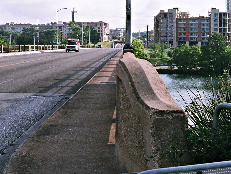 The Lamar Boulevard Bridge.<br /> <br /> For more than 50 years, the historic Lamar Boulevard Bridge carried cars, runners, walkers, and bicyclists over the section of the Colorado River known as Lady Bird Johnson Lake (formerly Town Lake). But over the years, as the volume of cars increased on the narrow roadway, the bridge became treacherous for pedestrians and bicyclists. Following two fatal pedestrian/car accidents in the early 1990s, City of Austin officials resolved to improve the bridge crossing for all users.<br /> <br /> It was not possible to make alterations and still preserve the bridge's historic character, so instead the city built another bridge adjacent to the existing structure. Partnerships and public involvement were crucial to the project -- engineers, architects, federal and state agencies, as well as Austin citizens contributed ideas to the bridge design.<br /> <br /> TE funds awarded in 1994, along with local bonds, were used to construct the James D. Pfluger, FAIA, Pedestrian/Bicycle Bridge, named after a distinguished Austin area architect. The 700-foot-long structure opened in June 2001. The bridge offers a safe transportation alternative for those traveling by foot, wheelchair, stroller or bicycle, and helps relieve traffic congestion. Benches along the bridge provide a community gathering place and allow users to sit and take in the breathtaking scenery of Austin's rolling hills. The bridge is now used by thousands of people every day.<br /> <br /> Federal Award: $953,252; Local Match: $305,041; Total: $1,258,293<br /> <br /> Photo by R.E. Martin