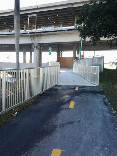 Photo Credit: Tracy Loh <br /> <br /> The construction of a bicycle and pedestrian path connecting the Dadeland South and Dadeland North metro stops in Miami, FL began in January of 2011. The project included the construction of a trail, a bicycle and pedestrian bridge over the entrance ramp to SR 878 along SR 5, lighting, signage, and fencing at the two metro stations. In addition to this, new signs and traffic signals were installed at the intersections with pedestrian ramps, intersections were repaved and restriped, and additional landscaping and paving was done.<br />  <br /> The project cost around $4.5 million and was completed in December 2011. The path provides a critical link between two popular Metrorail stations in the Miami-Dade area. The nearby streets are several lanes wide and merge with other major roadways. This path provides a safe and effective way to commute between the two stations and to elsewhere along the M-path.