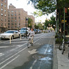 A major reconstruction project on Ninth Avenue in New York City, New York used $2 million in Transportation Enhancement funding to build separated bicycle lanes and to enhance the surrounding streetscape. The TE funding was matched by $14,700,000 in other funds and was used for the project which stretched from West 15th Street to West 23rd street. <br /> <br /> The project funded the reconstruction of 9th avenue and included the installation of new sidewalks, narrowing of the roadbed, landscaping, and pedestrian refuges. The main change was the addition of a physically-separated bicycle path which is one of the first urban on-street parking and signal-protected bicycle facilities in the US. The project has increased the safety of bicycling on the 70 foot wide avenue because the physically separated lane has an 8 ft. buffer of raised concrete islands or a parking lane. Additionally, pavement markings, signs, and discrete signal phases were added. The project won the 2008 Best Program Award from the Institute of Transportation Engineer's Transportation Planning Council.