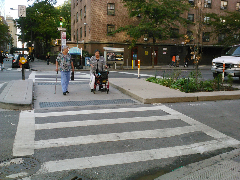 <b>These pedestrian shelters make crossing the street safer, easier, and less stressful for pedestrians who need more crossing time than allowed by the signal timing.</b>  A major reconstruction project on Ninth Avenue in New York City, New York used $2 million in Transportation Enhancement funding to build separated bicycle lanes and to enhance the surrounding streetscape. The TE funding was matched by $14,700,000 in other funds and was used for the project which stretched from West 15th Street to West 23rd street.   The project funded the reconstruction of 9th avenue and included the installation of new sidewalks, narrowing of the roadbed, landscaping, and pedestrian refuges. The main change was the addition of a physically-separated bicycle path which is one of the first urban on-street parking and signal-protected bicycle facilities in the US. The project has increased the safety of bicycling on the 70 foot wide avenue because the physically separated lane has an 8 ft. buffer of raised concrete islands or a parking lane. Additionally, pavement markings, signs, and discrete signal phases were added. The project won the 2008 Best Program Award from the Institute of Transportation Engineer's Transportation Planning Council.