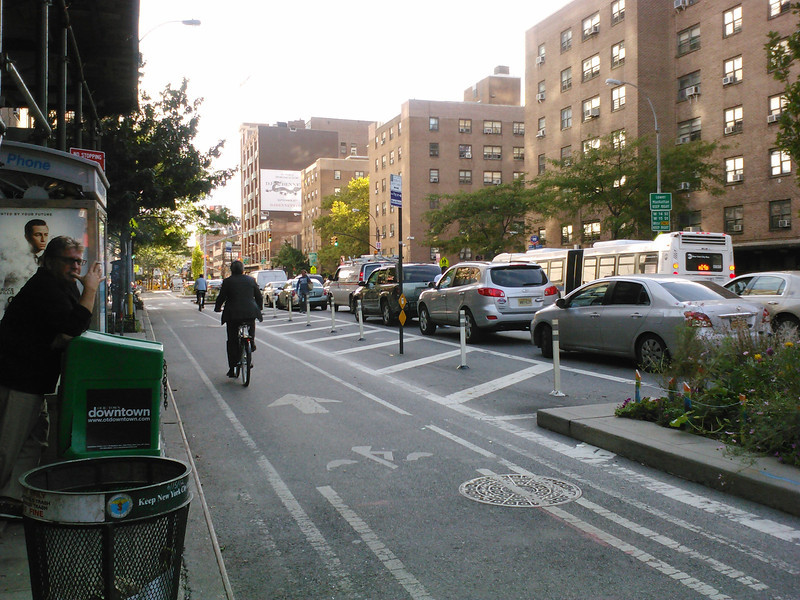 <b>An evening commuter beats the traffic in the Ninth Avenue cycletrack.</b>  A major reconstruction project on Ninth Avenue in New York City, New York used $2 million in Transportation Enhancement funding to build separated bicycle lanes and to enhance the surrounding streetscape. The TE funding was matched by $14,700,000 in other funds and was used for the project which stretched from West 15th Street to West 23rd street.   The project funded the reconstruction of 9th avenue and included the installation of new sidewalks, narrowing of the roadbed, landscaping, and pedestrian refuges. The main change was the addition of a physically-separated bicycle path which is one of the first urban on-street parking and signal-protected bicycle facilities in the US. The project has increased the safety of bicycling on the 70 foot wide avenue because the physically separated lane has an 8 ft. buffer of raised concrete islands or a parking lane. Additionally, pavement markings, signs, and discrete signal phases were added. The project won the 2008 Best Program Award from the Institute of Transportation Engineer's Transportation Planning Council.