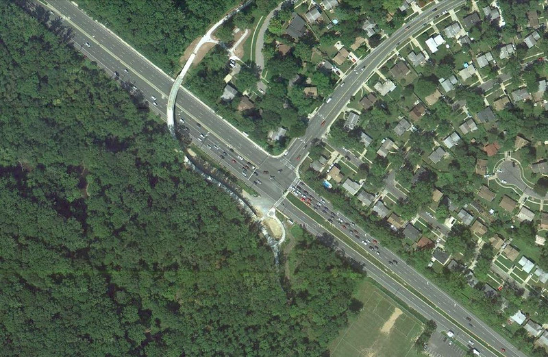 """Veirs Mill Rd. is a high volume road running from Wheaton, MD to Rockville, MD. As a result of this traffic, crossing Veirs Mill Road at Aspen Hill Road was slow and dangerous for pedestrians and bikers on Maryland's <a href=""""http://www.montgomeryparks.org/PPSD/ParkTrails/trails_MAPS/rock_creek.shtm""""> Rock Creek Hiker-Biker Trail</a>. The intersection at Aspen Hill Road featured an unsignalized crosswalk. In addition this section of trail was incomplete requiring navigation through local streets to continue on the trail. The Rock Creek Trail connects Rockville with Washington, D.C via 22 miles of trails.  To address the safety and congestion concerns in 2004 $3.95 million in TE funds were applied to a project to build a bicycle and pedestrian bridge over Veirs Mill. $5.15 million in local funds were also applied to the project. The construction of the bridge included trail connections to transit and communities, signage, lighting, stormwater management, aesthetics, and stairs. Construction of the project began in 2008 and finished in early 2011.   The project not only facilitates crossing Veirs Mill Road for bicyclists and pedestrians but also helps to reduce congestion for drivers. In 2003 Veirs Mill road had already been identified as having a failing level of service in the A.M. peak and P.M. peak times with congestion only supposed to increase. The existing at-grade crossings were dangerous and inconvenient to pedestrians and motorists alike. The new bridge has created a safe, attractive, and easy way for bicycles, pedestrians, and motorists to travel along or across Veirs Mill road."""