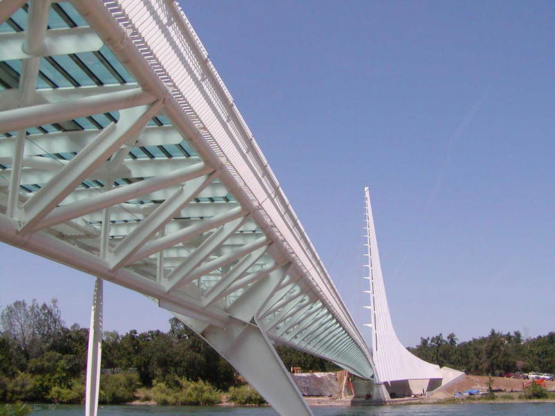 The dramatic design of the Sacramento River pedestrian and bicycle bridge befits Northern California's stunning scenery of volcanic mountains and lush forests. Santiago Calatrava, the renowned Spanish architect who designed the steel and glass structure, took his inspiration from the Sacramento River. He responded to the river's beauty and to the need to avoid disturbing the river's endangered Chinook salmon population. With no structures in the river, his resulting design seems to defy gravity. A steeply angled pylon on the riverbank supports the bridge with numerous steel cables. The pylon also acts as a giant sundial, glowing bright white in the noonday sun. The unique beauty of the bridge is nearly matched by its functionality; it safely conveys pedestrians across the river and connects a new natural sciences museum, an arboretum and a 32-mile network of riverside trails. A TE award received by the city of Redding for $1,371,000, along with the local matching funds, defrayed some of the bridge's $23.5 million total construction cost. The remaining costs were covered by the private McConnell Foundation.