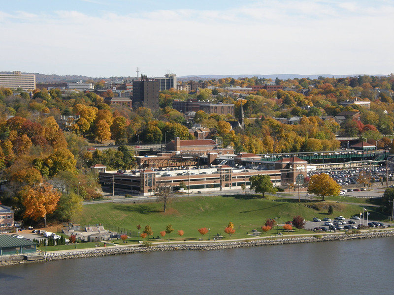 """Photo Credit: Melissa M.  <b>View of the Poughkeepsie Skate Park and Train Stations along waterfront</b>  The <a href=""""http://nysparks.state.ny.us/parks/178/details.aspx""""> Walkway Over the Hudson State Historic Park<a/> opened to the public in October of 2009. The walkway rests on the former Poughkeepsie-Highland Railroad Bridge which provided passage for freight and passenger trains between New York City and New England. The bridge was in service for nearly a century until a 1974 fire severely damaged the bridge. After the fire the bridge was out of service for decades.   In 1998 <a href=""""http://walkway.org/""""> Walkway Over the Hudson<a/>--a non-profit with the mission of connecting people to the Hudson Valley through stewardship of the State Historic Park--assumed ownership and began efforts to revitalize the bridge. In May of 2008 construction began. After the park opened an American Recovery and Reinvestment Act project was funded with $2.4 million through the TE program. The ARRA project aimed to increase access between the bridge and the waterfront and streets of Poughkeepsie, enhance multi-modal access between the walkway and the Poughkeepsie train station, and increase parking and facilities for persons with disabilities. The project will include a 21-story elevator, pathways along the waterfront and to the train station, and stair access on the eastside of the bridge.     The bridge has proven to be widely popular in its first year in providing people with a great place to walk, bike, rollerblade, or jog. With connections to the Dutchess County Rail Trail and Hudson Valley Rail Trail, the bridge makes it easier for local citizens and tourists to travel around the Hudson Valley. The trail has proven very popular, and actual use of the bridge is nearly 3 times higher than anticipated."""