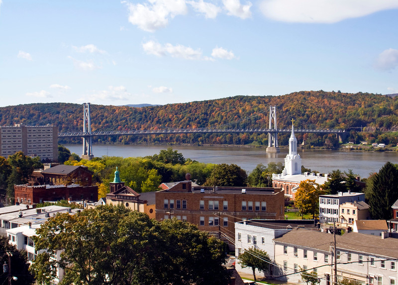 """Photo Credit: Ianqui Doodle  The <a href=""""http://nysparks.state.ny.us/parks/178/details.aspx""""> Walkway Over the Hudson State Historic Park<a/> opened to the public in October of 2009. The walkway rests on the former Poughkeepsie-Highland Railroad Bridge which provided passage for freight and passenger trains between New York City and New England. The bridge was in service for nearly a century until a 1974 fire severely damaged the bridge. After the fire the bridge was out of service for decades.   In 1998 <a href=""""http://walkway.org/""""> Walkway Over the Hudson<a/>--a non-profit with the mission of connecting people to the Hudson Valley through stewardship of the State Historic Park--assumed ownership and began efforts to revitalize the bridge. In May of 2008 construction began. After the park opened an American Recovery and Reinvestment Act project was funded with $2.4 million through the TE program. The ARRA project aimed to increase access between the bridge and the waterfront and streets of Poughkeepsie, enhance multi-modal access between the walkway and the Poughkeepsie train station, and increase parking and facilities for persons with disabilities. The project will include a 21-story elevator, pathways along the waterfront and to the train station, and stair access on the eastside of the bridge.     The bridge has proven to be widely popular in its first year in providing people with a great place to walk, bike, rollerblade, or jog. With connections to the Dutchess County Rail Trail and Hudson Valley Rail Trail, the bridge makes it easier for local citizens and tourists to travel around the Hudson Valley. The trail has proven very popular, and actual use of the bridge is nearly 3 times higher than anticipated."""