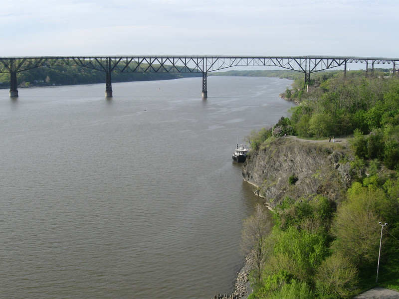 """Photo Credit: Kathryn Jones  The <a href=""""http://nysparks.state.ny.us/parks/178/details.aspx""""> Walkway Over the Hudson State Historic Park<a/> opened to the public in October of 2009. The walkway rests on the former Poughkeepsie-Highland Railroad Bridge which provided passage for freight and passenger trains between New York City and New England. The bridge was in service for nearly a century until a 1974 fire severely damaged the bridge. After the fire the bridge was out of service for decades.   In 1998 <a href=""""http://walkway.org/""""> Walkway Over the Hudson<a/>--a non-profit with the mission of connecting people to the Hudson Valley through stewardship of the State Historic Park--assumed ownership and began efforts to revitalize the bridge. In May of 2008 construction began. After the park opened an American Recovery and Reinvestment Act project was funded with $2.4 million through the TE program. The ARRA project aimed to increase access between the bridge and the waterfront and streets of Poughkeepsie, enhance multi-modal access between the walkway and the Poughkeepsie train station, and increase parking and facilities for persons with disabilities. The project will include a 21-story elevator, pathways along the waterfront and to the train station, and stair access on the eastside of the bridge.     The bridge has proven to be widely popular in its first year in providing people with a great place to walk, bike, rollerblade, or jog. With connections to the Dutchess County Rail Trail and Hudson Valley Rail Trail, the bridge makes it easier for local citizens and tourists to travel around the Hudson Valley. The trail has proven very popular, and actual use of the bridge is nearly 3 times higher than anticipated."""