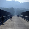 "Photo Credit: Katy Silberger  The <a href=""http://nysparks.state.ny.us/parks/178/details.aspx""> Walkway Over the Hudson State Historic Park<a/> opened to the public in October of 2009. The walkway rests on the former Poughkeepsie-Highland Railroad Bridge which provided passage for freight and passenger trains between New York City and New England. The bridge was in service for nearly a century until a 1974 fire severely damaged the bridge. After the fire the bridge was out of service for decades.   In 1998 <a href=""http://walkway.org/""> Walkway Over the Hudson<a/>--a non-profit with the mission of connecting people to the Hudson Valley through stewardship of the State Historic Park--assumed ownership and began efforts to revitalize the bridge. In May of 2008 construction began. After the park opened an American Recovery and Reinvestment Act project was funded with $2.4 million through the TE program. The ARRA project aimed to increase access between the bridge and the waterfront and streets of Poughkeepsie, enhance multi-modal access between the walkway and the Poughkeepsie train station, and increase parking and facilities for persons with disabilities. The project will include a 21-story elevator, pathways along the waterfront and to the train station, and stair access on the eastside of the bridge.     The bridge has proven to be widely popular in its first year in providing people with a great place to walk, bike, rollerblade, or jog. With connections to the Dutchess County Rail Trail and Hudson Valley Rail Trail, the bridge makes it easier for local citizens and tourists to travel around the Hudson Valley. The trail has proven very popular, and actual use of the bridge is nearly 3 times higher than anticipated."