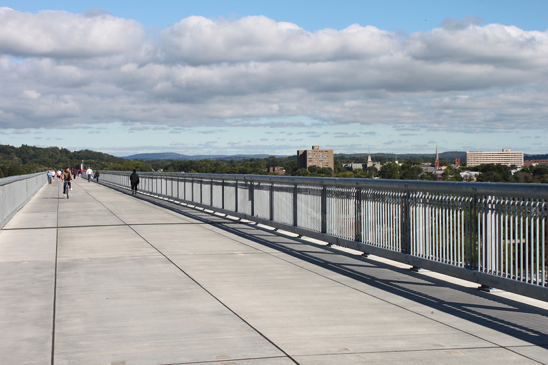 """Photo Credit: Joseph A  The <a href=""""http://nysparks.state.ny.us/parks/178/details.aspx""""> Walkway Over the Hudson State Historic Park<a/> opened to the public in October of 2009. The walkway rests on the former Poughkeepsie-Highland Railroad Bridge which provided passage for freight and passenger trains between New York City and New England. The bridge was in service for nearly a century until a 1974 fire severely damaged the bridge. After the fire the bridge was out of service for decades.   In 1998 <a href=""""http://walkway.org/""""> Walkway Over the Hudson<a/>--a non-profit with the mission of connecting people to the Hudson Valley through stewardship of the State Historic Park--assumed ownership and began efforts to revitalize the bridge. In May of 2008 construction began. After the park opened an American Recovery and Reinvestment Act project was funded with $2.4 million through the TE program. The ARRA project aimed to increase access between the bridge and the waterfront and streets of Poughkeepsie, enhance multi-modal access between the walkway and the Poughkeepsie train station, and increase parking and facilities for persons with disabilities. The project will include a 21-story elevator, pathways along the waterfront and to the train station, and stair access on the eastside of the bridge.     The bridge has proven to be widely popular in its first year in providing people with a great place to walk, bike, rollerblade, or jog. With connections to the Dutchess County Rail Trail and Hudson Valley Rail Trail, the bridge makes it easier for local citizens and tourists to travel around the Hudson Valley. The trail has proven very popular, and actual use of the bridge is nearly 3 times higher than anticipated."""