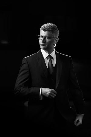 Black & White Portrait of a private security operative ( Close Protection ) with communication earpiece, photographed for his company´s branding portfolio.  Photographed by Ryan Cowan for Close Protection Services.