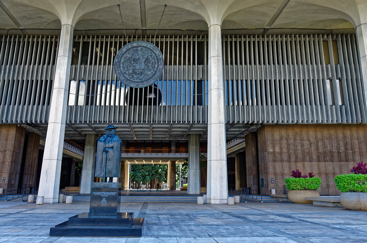 Hawai'i's State Capitol building was built in 1968. John Carl Warneke of San Francisco was the principal architect. The sculpture of Father Damien is the work of the French/Venezuelan artist Marisol Escobar. Damien was sainted by the Catholic Church in recognition of his selfless dedication in helping the lepers on Moloka'i, ultimately at the cost of his own life.
