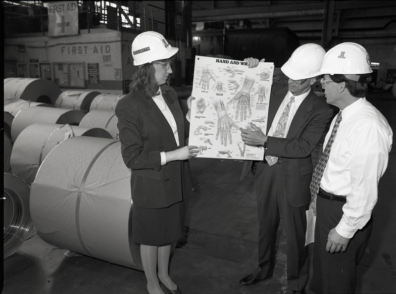 101494_636<br /> JANE DEHORN, J&L SPECIALITY STEEL: WORKMEN & HFH STAFF WEARING HARD HATS NEAR CONSTRUCTION SITE HOLDING ILLUSTATION, DETROIT 1996