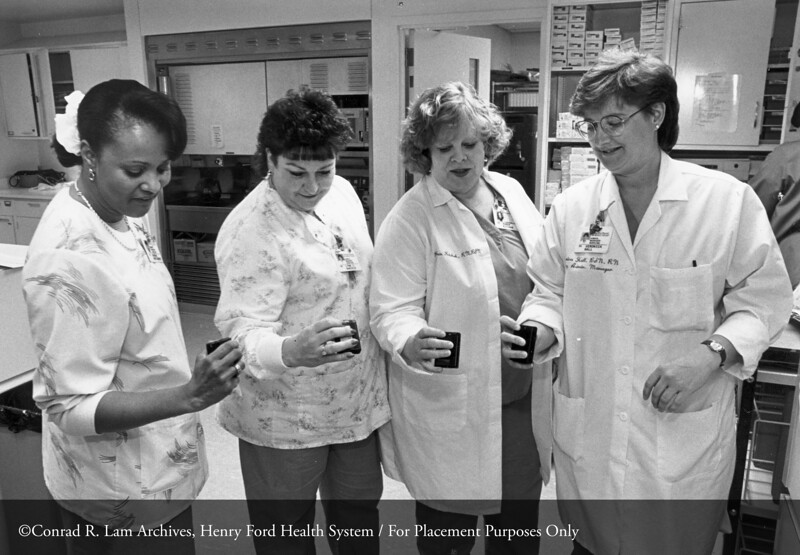 Marsha Montgomery, R.N., Lynn Daniels, R.N., Karen Kitchak, R.N. and Veronica (Ronnie) Hall, R.N., demonstrating their new pagers in Medical Critical Care Pod 3, c.1988
