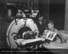 A Henry Ford Hospital polio patient reading to his son in 1946. From the Collections of The Henry Ford. THF117554 (core)