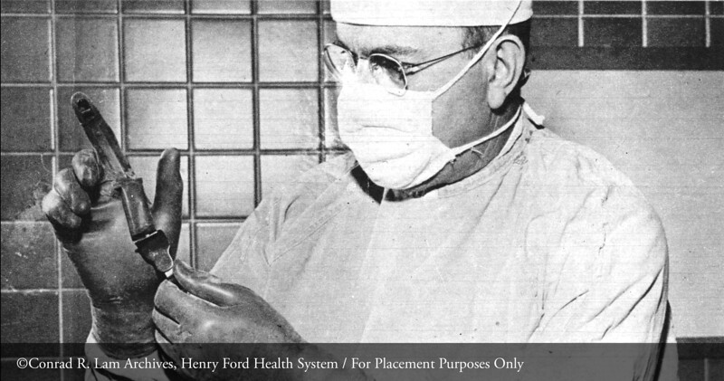Dr. Conrad R. Lam demonstrating the six finger glove, February 24, 1952. From the Conrad R. Lam Collection, Henry Ford Health System. (Credit: Detroit Free Press)