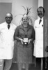 Drs. Gilbert Bluhm and John Sigler with Jeanne Riddle, Ph.D. displaying the American Medical Association Hektoen medal. From the Conrad R. Lam Collection, Henry Ford Health System. ID=08-043