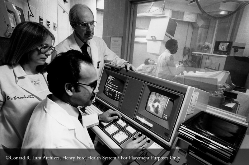 Dr. William R. Eyler with Debbie Erich, R.T., and Dr. P.C. Shetty with the diagnostic radiology digital video subtraction angiography unit to study the diseases of blood vessels, 1982. From the Conrad R. Lam Collection, Henry Ford Health System. ID=08-006