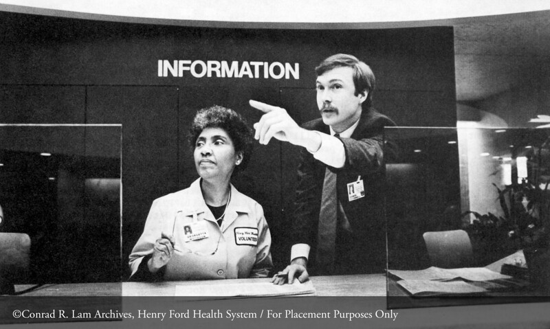 Georgetta Woodson, hospital volunteer and Dan O'Donnell at the Henry Ford Hospital information desk, 1985. From the Conrad R. Lam Collection, Henry Ford Health System. ID=09-041