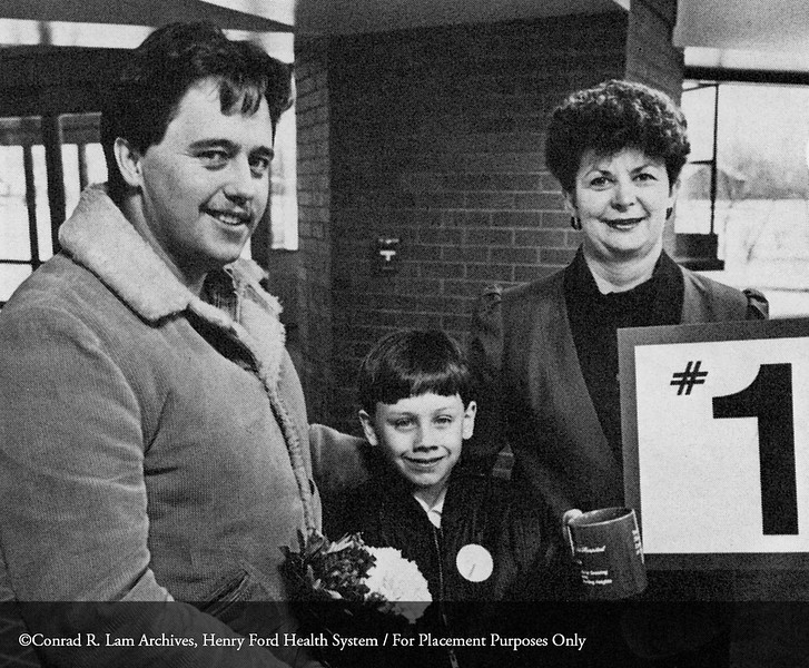 The first patient, Bryan Scott and his father of Sterling Heights, with V. Corej, administrative assistant for the Northwest Facilities at the Lakeside Medical Center, 1985. From the Conrad R. Lam Collection, Henry Ford Health System. ID=09-022