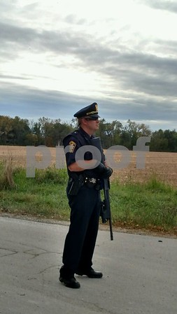 "LaSalle County Sheriff's deputies at the intersection of 14th Road and Route 34 block access to the woods south of Earlville, where Lowell Maxwell ""Max"" Ambler, suspected of an armed carjacking in Plainfield on Wednesday morning, was thought to be nearby as of 4 p.m."