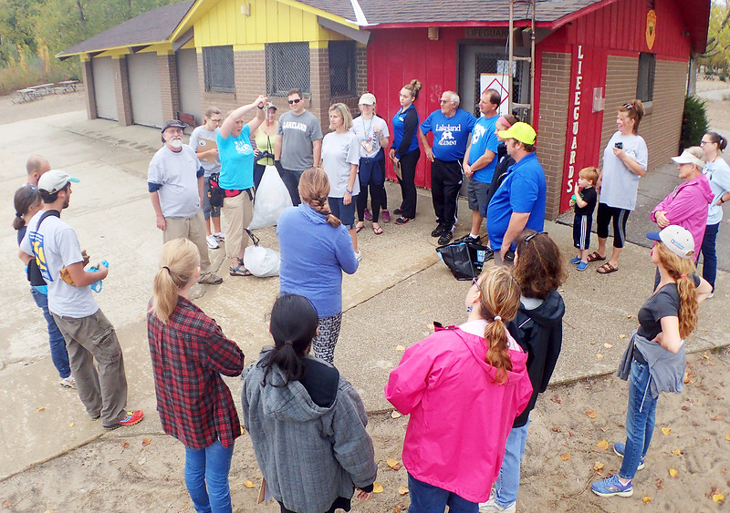 Jonathan Tressler — The News-Herald <br> Headlands Beach Clean-Up coordinator Katie Reynolds weighs one of the sacks of trash collected from the beach Oct. 6 by a group of volunteers from Lakeland Community College in conjunction with the school's 50 Acts of Service campaign and the Alliance for the Great Lakes' Adopt-a-Beach program.