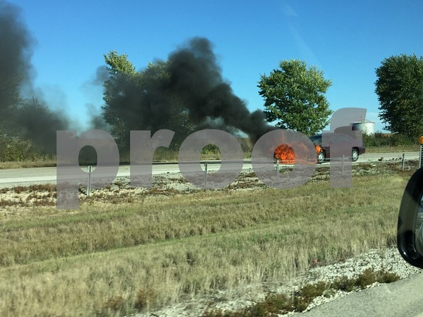 A maroon sedan spews flames from its front end Sunday afternoon on Interstate 88 on the east side of DeKalb.