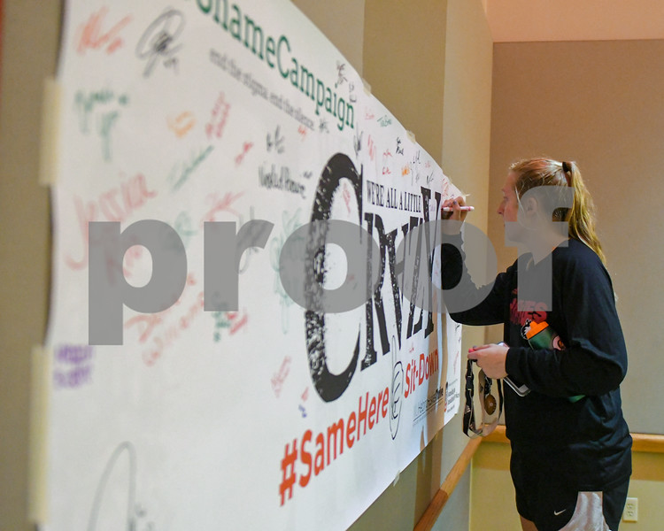 NIU Senior Meg Wolowicz signs a #NoShameCampaign #SameHere banner before the event that took place October 9th in the Duke Ellington Ballroom