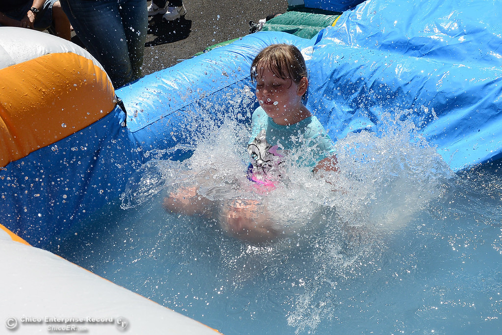 . McKenna Massey, 8, of Oroville, lands at the bottom of a slide with a splash as Feather Fiesta Days feature a parade, a car show, a chili cook off and more Saturday, May 13, 2017, in downtown Oroville, California. (Dan Reidel -- Enterprise-Record)