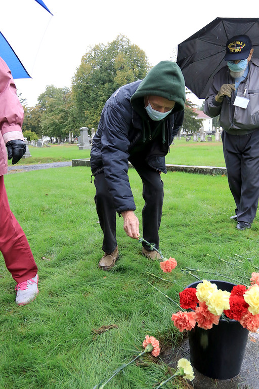 . A remembrance ceremony of the common burial site for the victims of the 1918-1919 influenza pandemic was held at the Evergreen Cemetery in Leominster on Saturday, October, 13, 2018. Tom Woodward places a flower at the marker for the one of the mass graves of people that died from the pandemic. They are all wearing face masks just they would have done during the pandemic. SENTINEL & ENTERPRISE/JOHN LOVE
