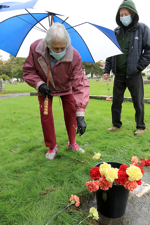 . A remembrance ceremony of the common burial site for the victims of the 1918-1919 influenza pandemic was held at the Evergreen Cemetery in Leominster on Saturday, October, 13, 2018. Nancy Piermarini places a flower at the marker for the one of the mass graves of people that died from the pandemic. They are all wearing face masks just they would have done during the pandemic. SENTINEL & ENTERPRISE/JOHN LOVE
