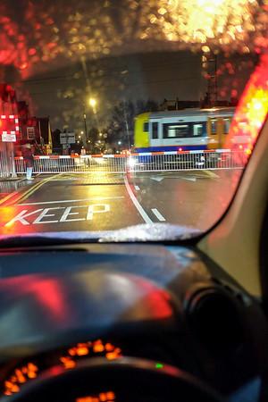 car waiting at level crossing at night, UK