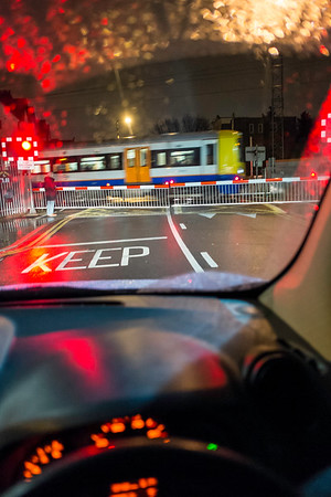 car waiting at level crossing at night, UK