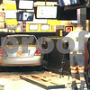 Eric R. Olson –eolson@shawmedia.com<br /> A tow truck driver clears away debris before removing a Hyundai Elantra from the inside of the Buffalo Wild Wings restaurant in DeKalb on Tuesday evening. Police said the driver was distracted and hit the gas pedal by mistake.
