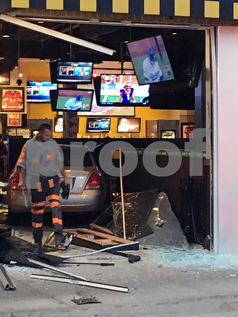 Eric R. Olson – eolson@shawmedia.com<br /> A tow truck driver clears away debris before removing a Hyundai Elantra from the inside of the Buffalo Wild Wings restaurant in DeKalb on Tuesday evening. Police said the driver was distracted and hit the gas pedal by mistake.