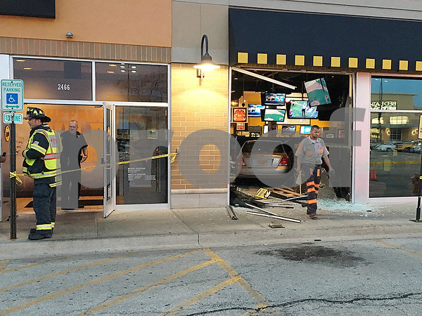 Eric R. Olson – eolson@shawmedia.com<br /> Police, firefighters and a tow truck driver at the scene where a vehicle crashed through the front of the DeKalb Buffalo Wild Wings restaurant on Tuesday. Police said the driver was distracted and hit the gas pedal by mistake.