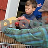 Sycamore History Museum volunteer John Prendergast (right) holds the apple press lid open while Ronin Rasmussen, 7, of Chicago drops a few apples into it to make apple cider Sunday during the Sycamore History Museum's Fall Festival.