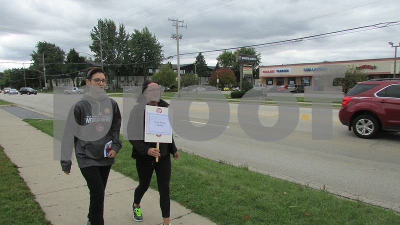 Angie Shaulis (left) and Jenny Swanson, both Hope Haven employees, begin walking during the Sondra King Memorial CROP Hunger Walk to raise money for both local food pantries and nonprofit organizations that help fight hunger in third-world countries. Walkers began at Westminster Presbyterian Church in DeKalb.