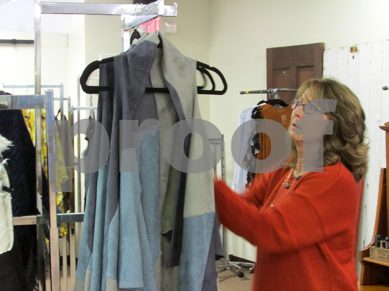 Jana Nowak, owner of Blu Door Decor, organizes clothing at her store on 209 E. Lincoln Highway. This site is scheduled for demolition next year as part of the $6 million Plaza DeKalb development.
