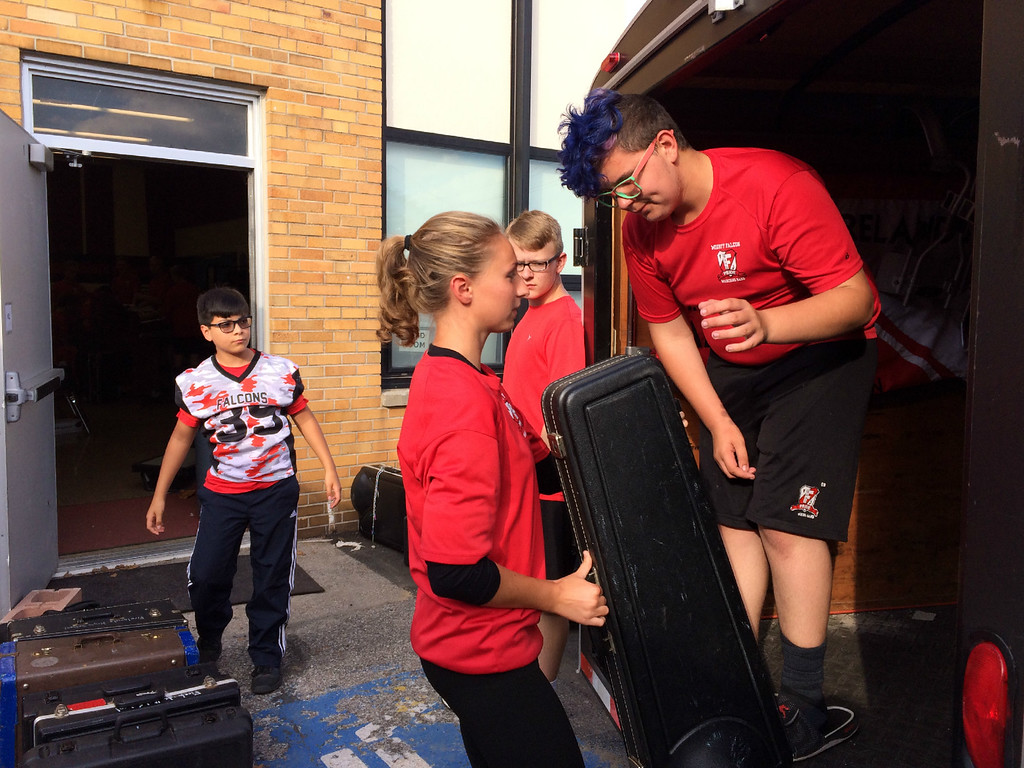 . Carol Harper � The Morning Journal <br> Helper Santos Silva and Firelands High School students Rebecca Hopkins, Jackson Thomas, and William Krejci pack instruments into a band trailer Oct. 13, 2017, at Firelands High School at 10643 Vermilion Road in rural Oberlin.