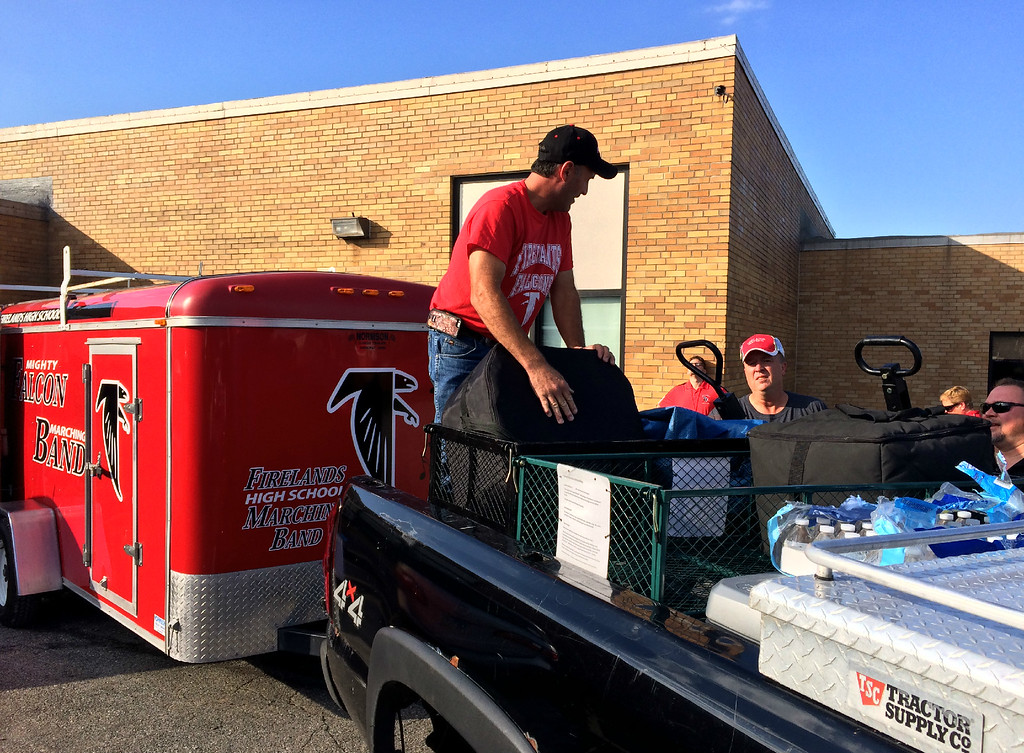 . Carol Harper � The Morning Journal <br> Volunteers Chris Whitter, Tim Born and Jason Smith load equipment onto a pickup truck Oct. 13, 2017, preparing for two days of Firelands Marching Band performances at a football game and band competition at The Ohio State University Stadium in Columbus.