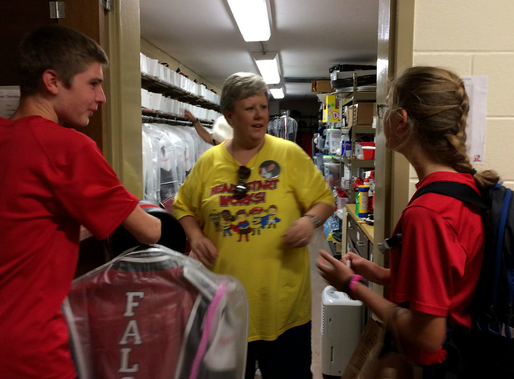 . Carol Harper � The Morning Journal <br> Firelands High School Marching Band members Nathaniel Boucher and Grace Sherban collect uniforms from volunteer Shannon Smith before an away football game Oct. 13, 2017, at the school at 10643 Vermilion Road in rural Oberlin.