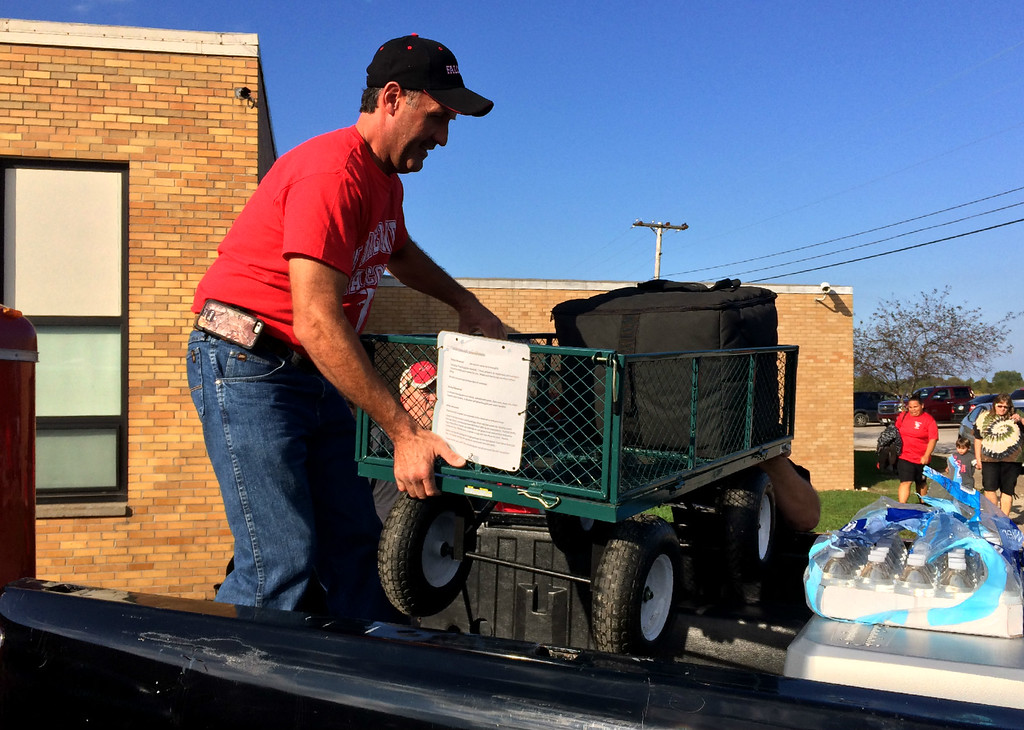. Carol Harper � The Morning Journal <br> With help from below, volunteer Chris Whitter loads a band equipment cart into a pickup truck Oct. 13, 2017, at Firelands High School at 10643 Vermilion Road in rural Oberlin for a weekend trip of two performances by the Firelands High School Marching Band.