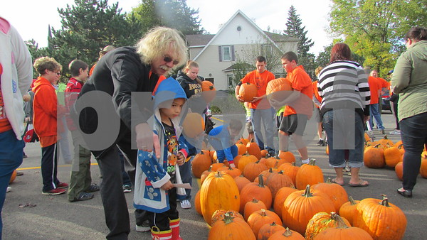 Denis Jagodzinski helps Terrence Jarmon, 5, of Genoa choose a pumpkin during Jagodzinski's annual pumpkin giveaway Saturday leading up to the Sycamore Pumpkin Festival.