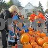Denis Jagodzinski helps Terrence Jarmon, 5, of Genoa choose a pumpkin during Jagodzinski's annual pumpkin giveaway Saturday leading up to the Sycamore Pumpkin Festival.