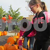 Ashlyn Fredrickson (bending down), 9, of Cortland and Jozlyn Baird, 9, of Cortland look at pumpkins during Denis and Jill Jagodzinski's annual pumpkin giveaway Saturday in downtown Sycamore.