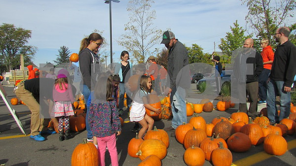 Families choose pumpkins during Denis and Jill Jagodzinski's annual pumpkin giveaway Saturday near the Wally Thurow statue in downtown Sycamore.