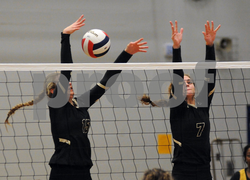 Sycamore players Hunter Morgan (15) and Faith Reynolds (7) go up to block against Kaneland in the Burlington Central Regional tournament on Tuesday night.  Steve Bittinger - For Shaw Media