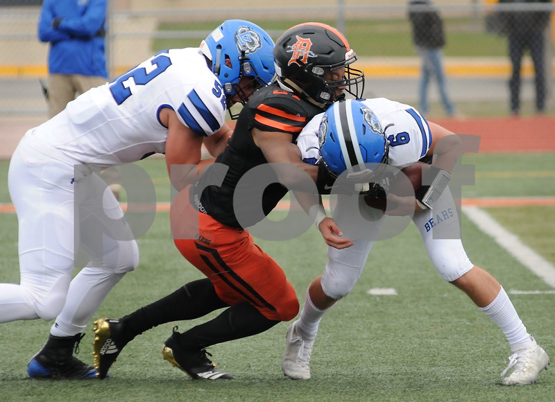 Jalon Redmond of DeKalb beats a block to take down Lake Zurich quarterback Jack Moses during playoff action Saturday in DeKalb.  Steve Bittinger - For Shaw Media