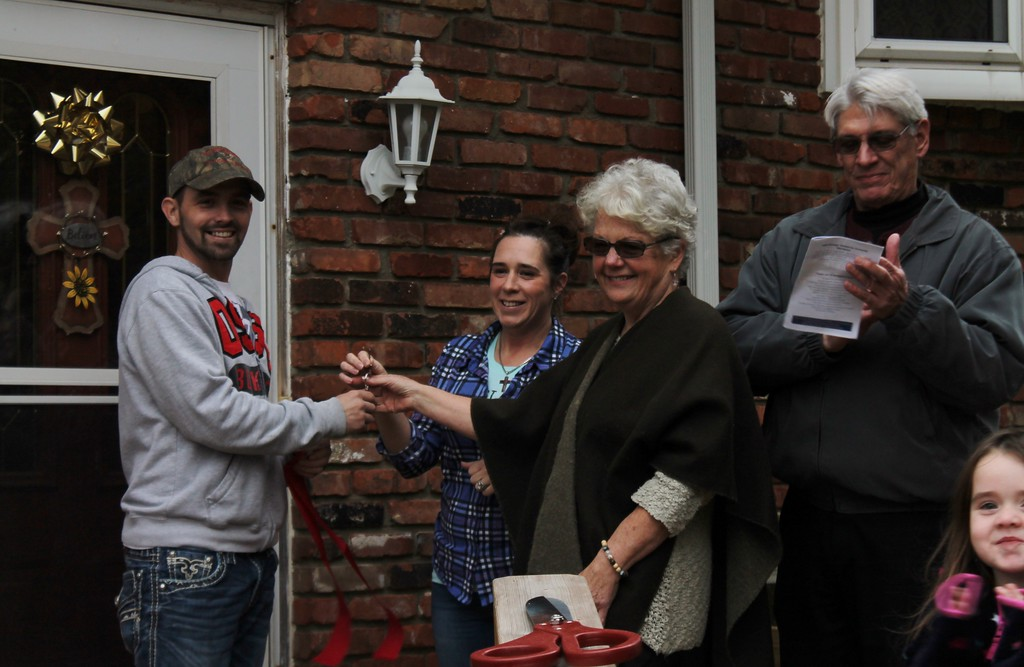 . Kristi Garabrandt - The News-Herald  William Meyer and Mary Huge present the keys of the completed house to Bryan and Heather at the Oct. 29 dedication.