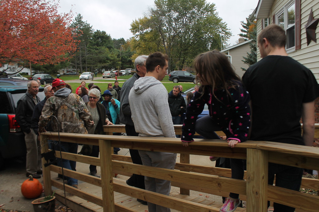 . Kristi Garabrandt - The News-Herald Friends, family and workers gather at the home dedication for the rehabbed house of Bryan and Heather on Oct. 29.